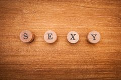 Inscription sexy composed of wooden letters on a wooden background. Indicates courage, beauty, mystery. And sex stock photography
