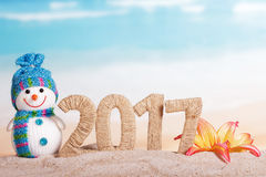Inscription 2017 snowman and flower in sand against sea. Royalty Free Stock Images