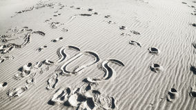 Inscription SOS and footprints. In the sand stock photography