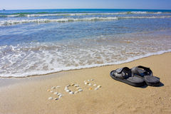 Inscription SOS in the sand with slippers. And boat on skyline Stock Photo