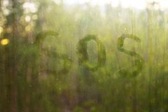 The inscription `SOS` written by a finger on a dirty window glass. Front view. royalty free stock photo