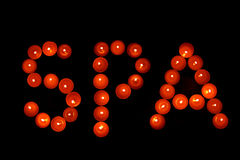 The inscription Spa of red candles on a dark background. Stock Image