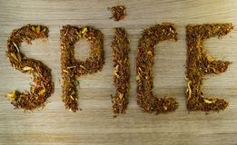 Inscription spice, made with a mixture of spices on a cutting wooden board royalty free stock photo
