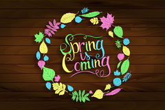 Inscription Spring is coming on wooden background. In a frame of colored leaves. Hand draw, vector illustration. Graphic design Royalty Free Stock Photo