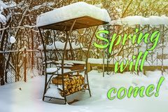 Inscription Spring will come. Grill in snowdrift. Chopped firewood from pine and birch for bbq under the snow on the street. stock photography