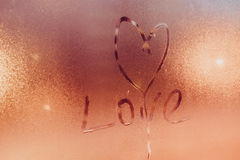 Inscription on steamy glass - heart symbol and love word Royalty Free Stock Image