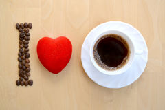 Inscription still life of I love coffee on a light board background. Coffee grains, red heart, a white cup with coffee stock photos