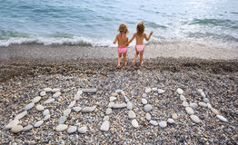 Inscription from stones BEACH at coast, two girls Royalty Free Stock Photos