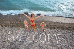 Inscription from stones WELCOME at coast, family Stock Photography