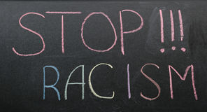 Inscription of stop racism. With multi-colored chalk on a slate Royalty Free Stock Photo