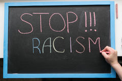 Inscription of stop racism. An inscription of stop racism with a multi-colored chalk on a slate in a blue frame and a hand with chalk that adds it Stock Image