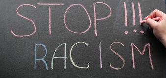 Inscription of stop racism. An inscription of stop racism with a multi-colored chalk on a slate in a blue frame and a hand with chalk that adds it Royalty Free Stock Photo