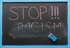 Inscription of stop racism. An inscription of a stop racism with a multi-colored chalk on a slate in a blue frame and a sponge with which the inscription is Royalty Free Stock Photography