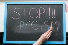 Inscription of stop racism. An inscription of a stop racism with a multi-colored chalk on a slate and a hand with a sponge wiping it Stock Photography