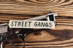 Inscription STREET GANGS on torn paper and glossy pistol. On old rustic wooden weathered planks stock photo