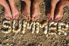 The inscription SUMMER laid out of shells on the sand