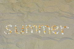 The inscription Summer is laid out from shells on the sand. On the beach Royalty Free Stock Photo