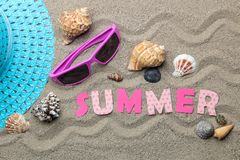 Inscription summer from paper of multi-colored letters and seashells and summer accessories on the sea sand. Summer. relaxation. v. Acation. top view stock image