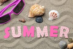 Inscription summer from paper of multi-colored letters and seashells and summer accessories on the sea sand. Summer. relaxation. v. Acation. top view stock images