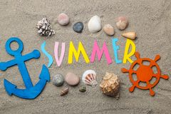 Inscription summer from paper of multi-colored letters and seashells and summer accessories on the sea sand. Summer. relaxation. v. Acation. top view stock photography