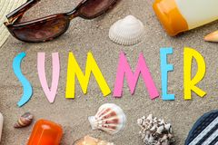 Inscription summer from paper of multi-colored letters and seashells and summer accessories on the sea sand. Summer. relaxation. v. Acation. top view royalty free stock image