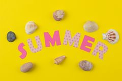 Inscription summer from paper of multi-colored letters and seashells on a bright yellow background. Summer. relaxation. vacation stock photo