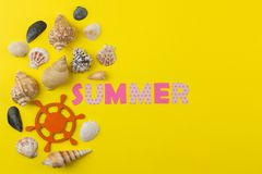 Inscription summer from paper of multi-colored letters and seashells on a bright yellow background. Summer. relaxation. vacation stock photography