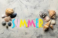 Inscription summer from paper of multi-colored letters and seashells on a light background. Summer. relaxation. vacation. top view. Inscription summer from paper stock images