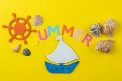 Inscription summer from paper of multi-colored letters and seashells and a ship on a bright yellow background. Summer. relaxation. Vacation stock images