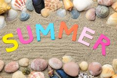 Inscription summer from paper of multi-colored letters and seashells and summer accessories on the sea sand. Summer. relaxation. v. Acation. top view royalty free stock photography