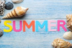 Inscription summer from paper of multi-colored letters and seashells and summer and sea accessories on a blue wooden table. Summer. Relaxation. vacation. top stock photo