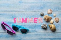 Inscription summer from paper of multi-colored letters and seashells and summer and sea accessories on a blue wooden table. Summer. Relaxation.  vacation. top stock photos