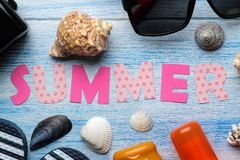 Inscription summer from paper of multi-colored letters and seashells and summer and sea accessories on a blue wooden table. Summer. Relaxation. vacation. top royalty free stock photo
