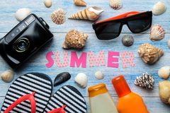 Inscription summer from paper of multi-colored letters and seashells and summer and sea accessories on a blue wooden table. Summer. Relaxation. vacation. top stock image