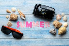 Inscription summer from paper of multi-colored letters and seashells and summer and sea accessories on a blue wooden table. Summer. Relaxation. vacation. top stock images