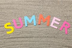 Inscription summer paper multicolored letters on the sea sand. Summer. relaxation. vacation. top view stock images