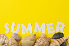 The inscription summer of paper white letters and seashells on a bright yellow background. Summer. relaxation. vacation. top view. The inscription summer of royalty free stock images