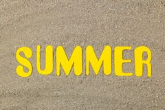 Inscription summer of paper yellow letters on the sea sand. Summer. relaxation. vacation. top view stock photos
