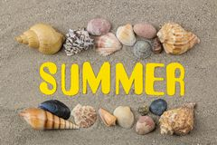Inscription summer of paper yellow letters and seashells on the sea sand. Summer. relaxation. vacation. top view stock photography