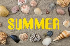 Inscription summer of paper yellow letters and seashells on the sea sand. Summer. relaxation. vacation. top view royalty free stock photography