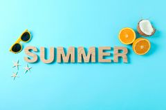 Inscription summer with starfishes, oranges, coconut and sunglasses on color background, space for text stock photo