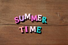 Inscription summertime by multicoloured wooden letters on wooden background. Concept happy summertime royalty free stock image