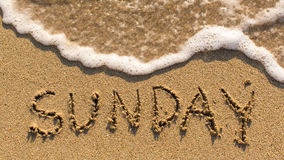 Inscription SUNDAY on a gentle beach sand with the soft wave. Royalty Free Stock Photos