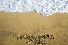 Inscription sur le sable au sujet des vacances 2010 Image libre de droits