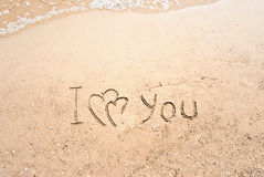 Inscription sur le sable je t'aime Photos stock