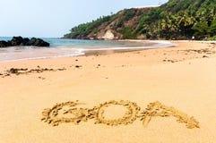 Inscription sur le sable L'inscription Goa sur une plage sablonneuse contre la mer bleue et la turquoise arrosent et des vagues Photographie stock