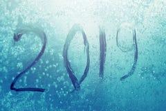 Inscription 2019 sur une fenêtre congelée à l'arrière-plan de glace de gelée de couleur de turquoise Lumière du soleil par le mod photo stock