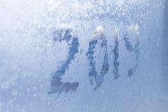 Inscription 2019 sur une fenêtre congelée dans des nombres rayés par gelée sur le fond froid bleu d'hiver photo stock