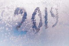 Inscription 2019 sur une fenêtre congelée dans des nombres rayés par gelée sur le fond froid bleu d'hiver image stock
