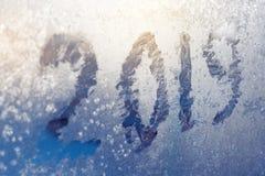 Inscription 2019 sur une fenêtre congelée dans des nombres rayés par gelée sur le fond froid bleu d'hiver photographie stock